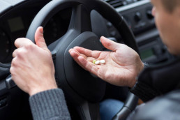 Drug driving concept - man has pills in his palm in his car