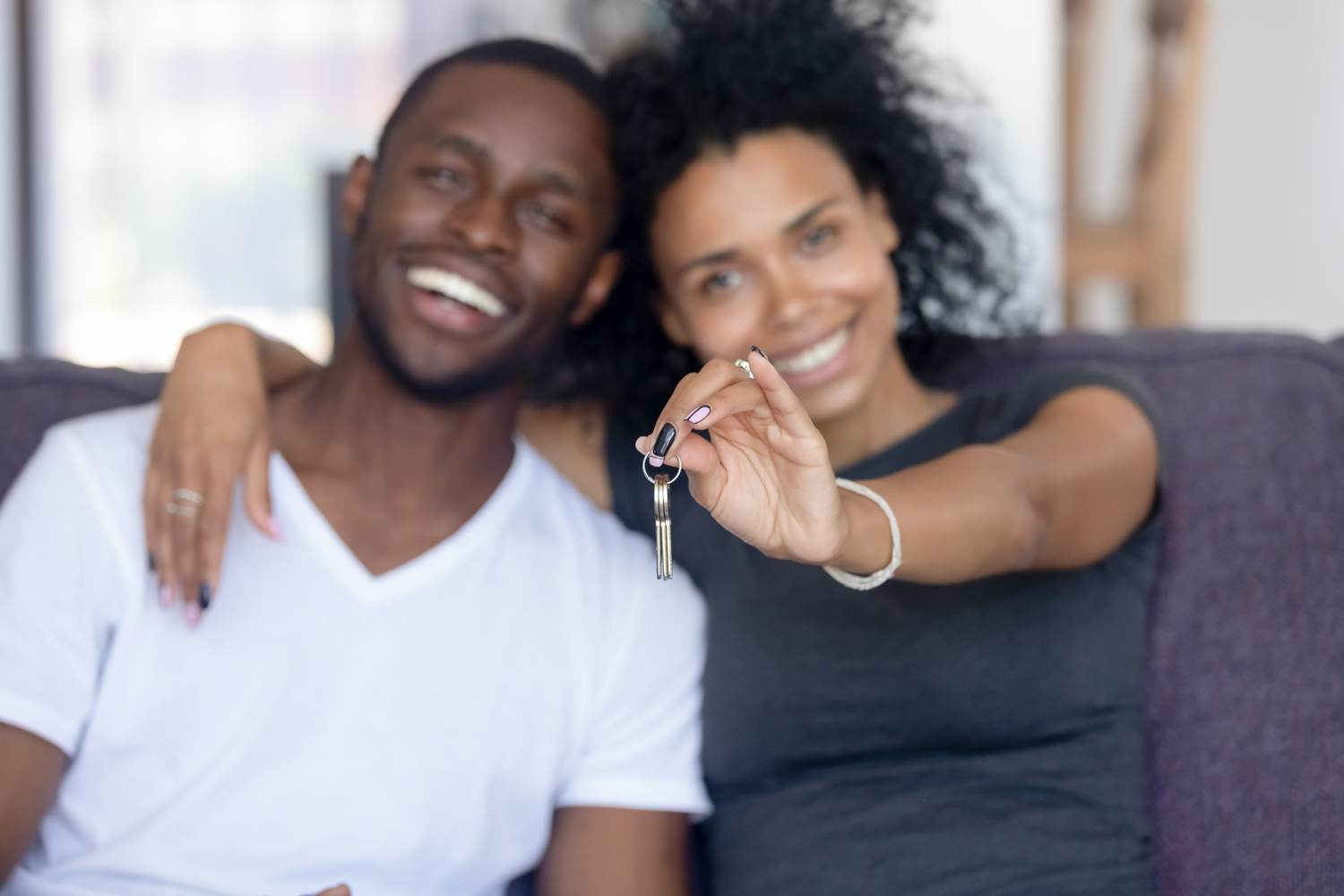 Couple purchase property woman holding keys