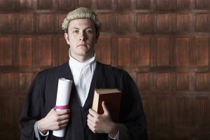 lawyer in wig and robe holding a large book in a courtroom
