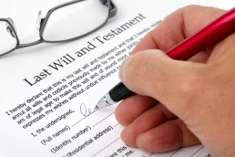 Close up of a hand signing a Last Will and Testament document