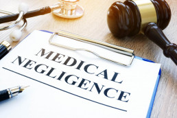 Medical negligence typed on sheet of paper on a clipboard, gavel in the background