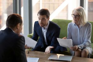 Concerned businesspeople argue with colleague or client dissatisfied with contract terms