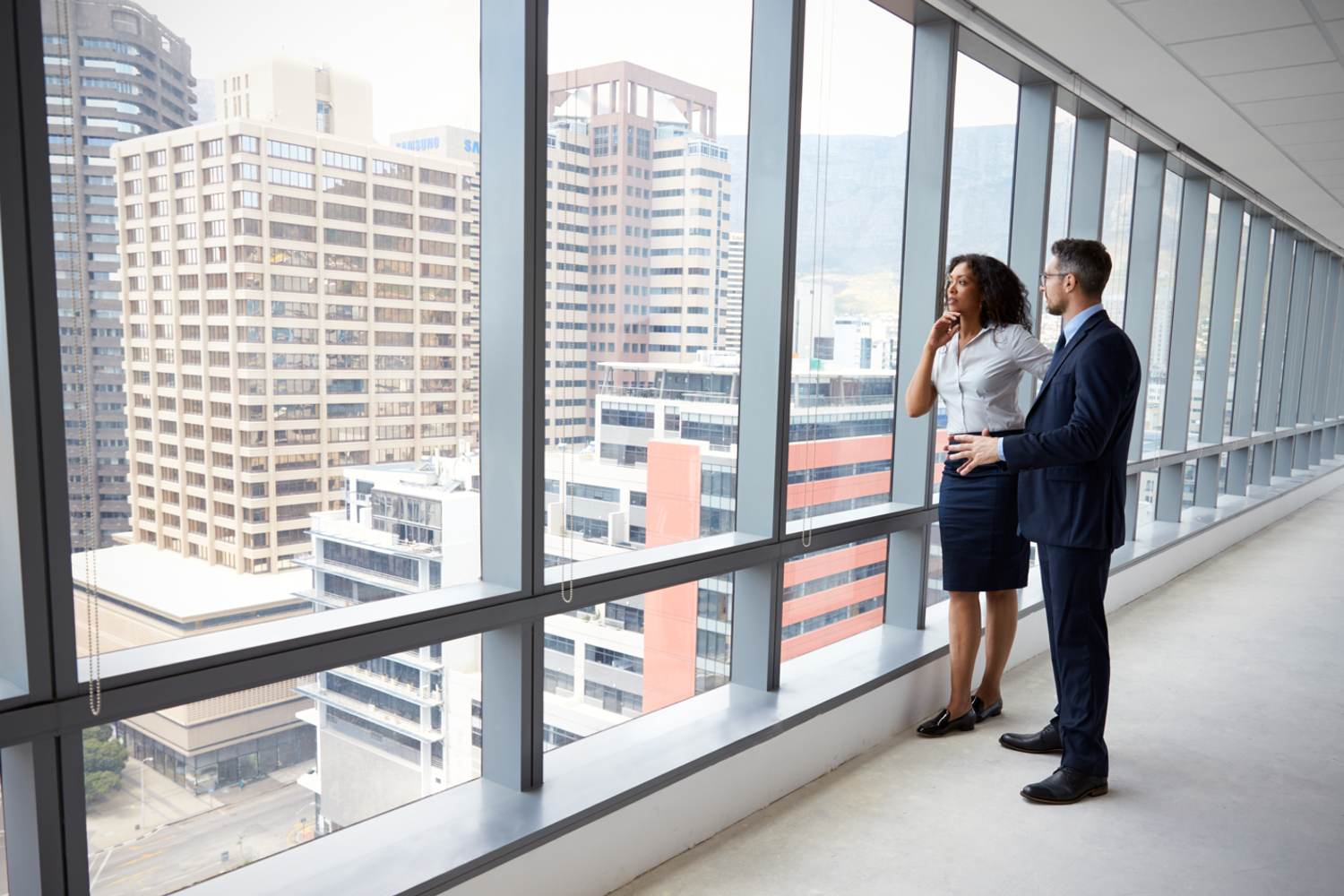 Businesswoman admiring view from commercial property window - commercial property solicitors