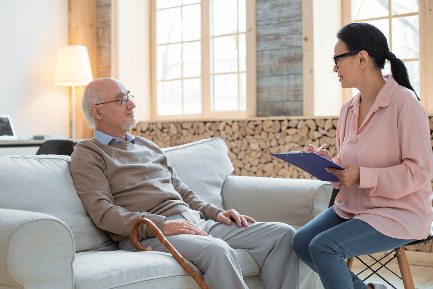 Caregiver assessing the wellbeing of senior adult