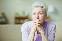 Elderly woman lost in thought