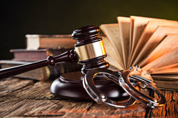 Gavel, old books and handcuffs on wooden desk